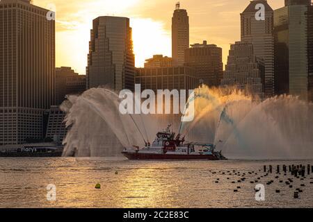 El barco FDNY rocía agua roja, blanca y azul antes de los fuegos artificiales del 4 de julio de Macy