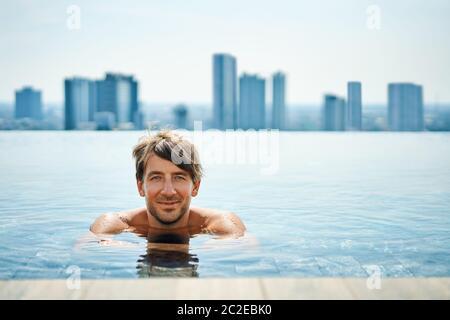 Hombre guapo Relájate en la piscina