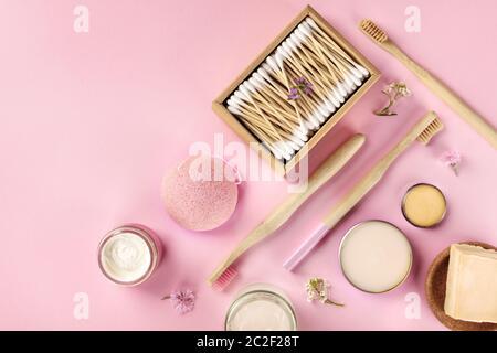 Cosméticos sin plástico, sin residuos, planos sobre un fondo rosa. Cepillos de dientes de bambú y hisopos de algodón, esponja konjac, natural
