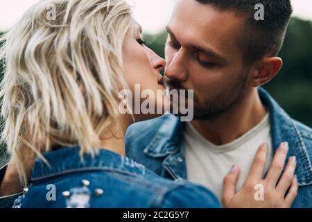 Pareja joven y cariñosa besando y disfrutando de la compañía de los demás al aire libre