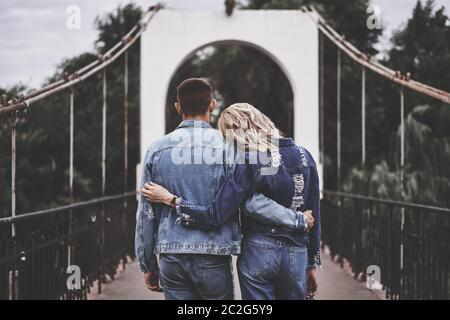 Vista trasera de una pareja abrazándose alojándose en el puente y disfrutando del descanso