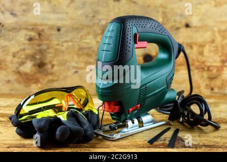 Una herramienta de poder de rompecabezas, gafas protectoras, guantes y hojas para rompecabezas eléctricos sobre fondo de madera vintage.