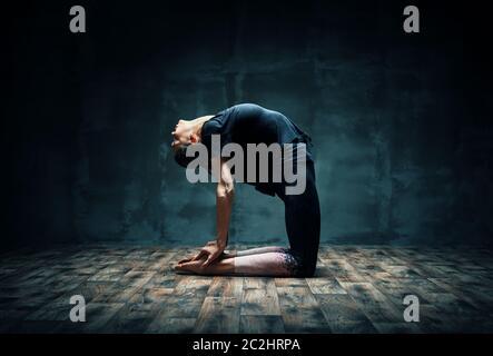 Mujer joven practicando yoga haciendo postura Camel en la habitación oscura