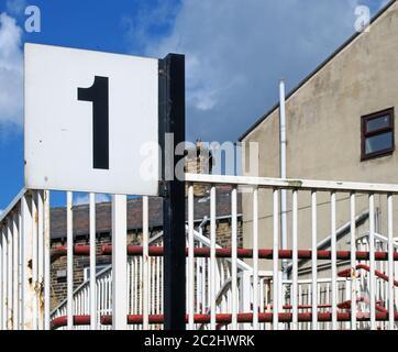 una señal de plataforma de la estación de tren con el número 1 junto a las barandillas pintadas en mal estado en una pequeña estación de tren local en el norte de eng Foto de stock