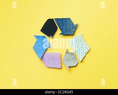 Reducir, reutilizar, reciclar el concepto de fondo. Símbolo de reciclado de ropa usada sobre fondo amarillo. Vista superior plana o de laicos.