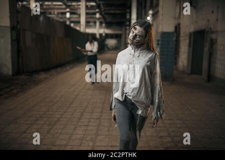 Hombre con hacha que captura a zombi hembra en una fábrica abandonada, lugar aterrador. Horror en la ciudad, crawlies espeluznantes, Apocalipsis de los días de los doomsday, monstruos malvados sangrientos