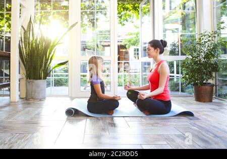 Joven morena con una pequeña hija en un uniforme deportivo haciendo yoga Foto de stock