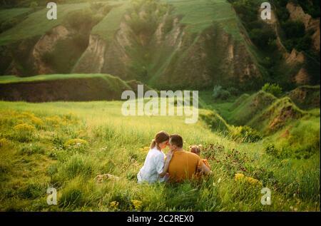 Familia con una hija pequeña descansa mientras camina en el prado sobre el fondo del barranco. Vista posterior.