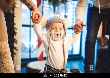 Divertido niño pequeño de 1 año de edad de aprendizaje caminar a casa en invierno en una casa de año Nuevo decorado. Papá y mamá de la familia joven sostienen por th Foto de stock