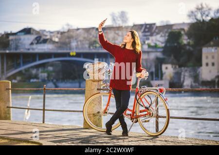 Una hermosa joven con una bicicleta roja retro está haciendo una foto de sí misma en la vieja ciudad de Europa en el río Rin