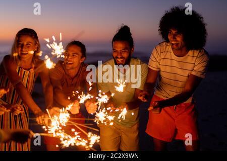 Grupo multiétnico de hombres y mujeres bailando con palo de fuego Foto de stock