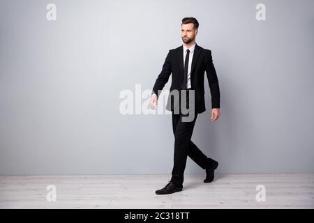 Foto lateral de perfil de tamaño completo de elegante y guapo economista trabajador ir a caminar al lugar de trabajo reunión ropa pantalones de moda pantalones aislados sobre color gris