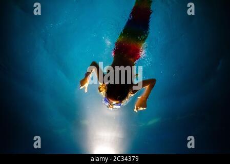 Niña disfrazada de sirena buceando hacia la luz de una piscina azul, con un fondo de ensueño de aguas cristalinas.