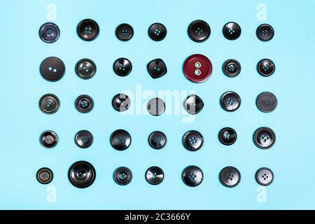 Vista superior del botón rojo entre muchos botones negros sobre fondo azul.