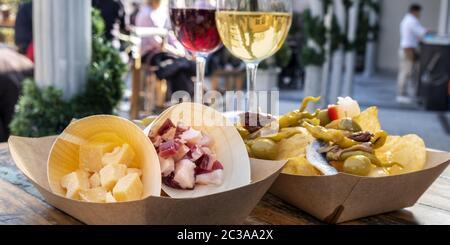 Panorama del bar de tapas. Queso, jamón y pinchos con vino tinto y blanco sobre una mesa de madera en una cafetería al aire libre