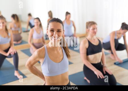 Retrato de un joven y alegre instructor de yoga relajándose después de dar clases de yoga a un gran grupo de gente deportiva atractiva. Activo sano l