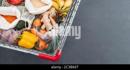 Frutas, verduras, granos en bolsas de tela reutilizables en el carrito de compras. Vista superior o plano. Espacio de copia. Carro con primeros planos de comida, disparo de estudio. Fo