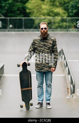 Hombre barbudo sosteniendo el longboard o el skateboard en el parque.