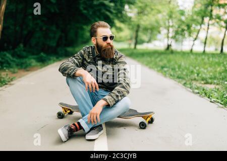 Joven barbudo hombre longboarder con ropa informal sentado en el longboard o skateboard al aire libre. Concepto urbano, subcultural, skateboard