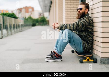 Joven barbudo sentado en su monopatín en un parque de patinaje.