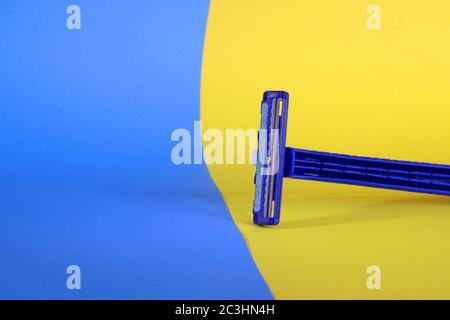 Un primer plano de una navaja azul de dos hojas sobre un fondo amarillo-azul