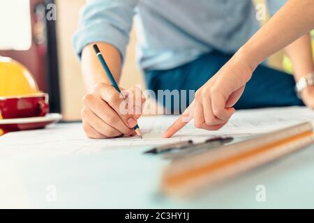 ingenieros que sostienen un bolígrafo que señala un edificio y el diseño de un plan de construcción de la instalación como guía para los constructores con detalles