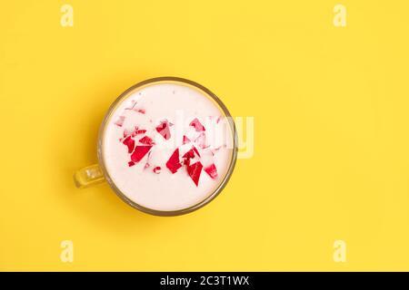 Leche de luna rosa ayurvédica en una copa de vidrio sobre fondo amarillo con espacio para texto Foto de stock