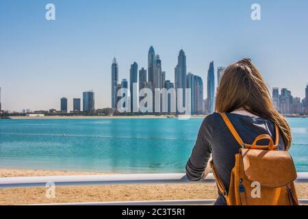 Una joven mirando el puerto deportivo de Dubai desde la playa de Palm Jumeirah durante un día soleado, Dubai, Emiratos Árabes Unidos