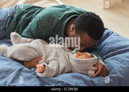 Retrato de un padre afroamericano que le encanta besar a un bebé lindo mientras se encuentra en la cama en el acogedor interior de la casa, espacio para copias