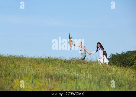 feliz familia con niña lanza cometa al aire libre en la naturaleza de verano Foto de stock