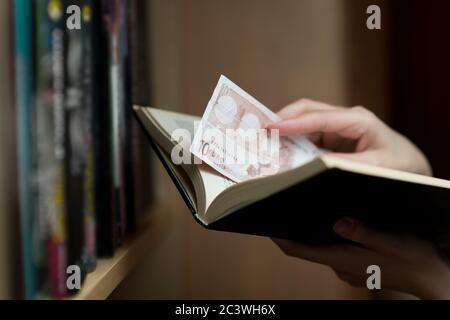 la mano de la chica pone o saca ahorros en euros de un libro de papel. Pequeños ahorros