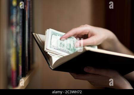 la mano de la chica pone o saca ahorros en dólares de un libro de papel Foto de stock