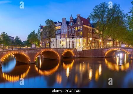 Calles y canales de Ámsterdam durante el anochecer. Puentes iluminados, temporada de verano. Destino turístico popular para los turistas.