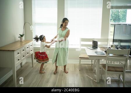 Chica disfruta de una clase de baile en línea con un ordenador portátil conectado a una televisión en casa
