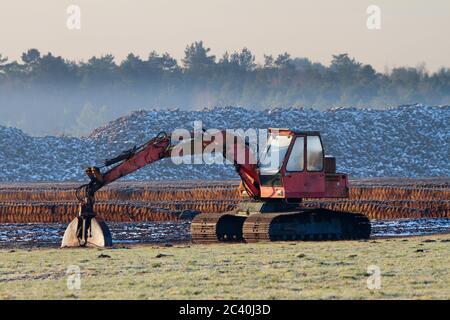 Arrastre de turba frente a un campo de extracción de turba Foto de stock