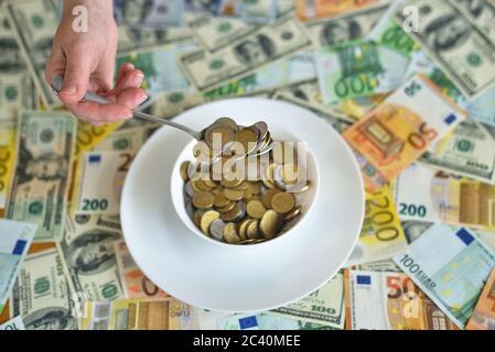 plato con monedas. billetes en euros y dólares en la mesa
