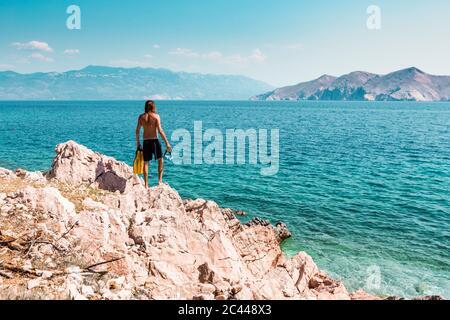 Croacia, Krk, hombre de pie sobre la roca y mirando al mar