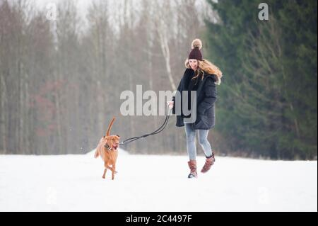 Feliz joven corriendo con perro en la nieve contra los árboles en el bosque durante el invierno