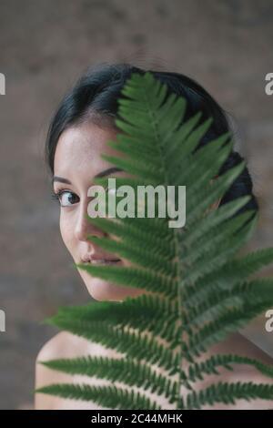 Hermosa mujer joven escondida detrás de las hojas de helecho