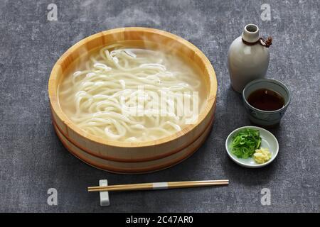 kamaage udon es una especie de plato japonés udon noodes, fideos udon caliente en cubo de madera y salsa de inmersión