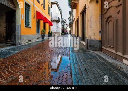 Charco en la calle adoquinada entre casas antiguas en la ciudad de Alba, Piamonte, norte de Italia.