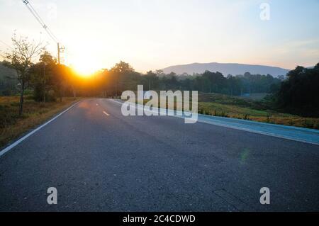 Un largo camino de curvas en la montaña al amanecer
