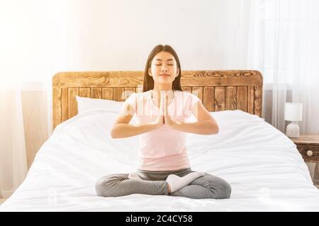 Chica relajante haciendo yoga sentado en posición de loto en casa Foto de stock