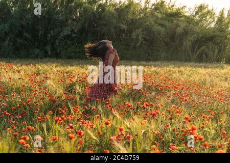 Joven morena en un vestido rojo con grabados corriendo con su pelo en el viento en medio de un campo de amapola rodeado por un bosque Foto de stock