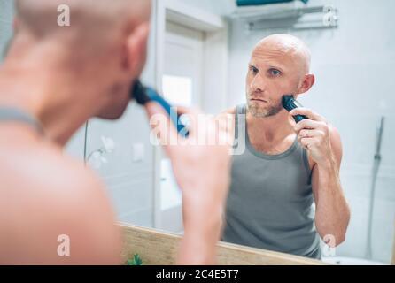 Hombre calvo fijando su barba mirando en el espejo del baño utilizando un eléctrico recargable Beard Trimmer. Tratamientos rutinarios para el cuidado de la piel y el cuerpo a diario