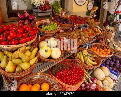 Frutas y verduras frescas que se muestran en las cestas fuera de un greengrocers italiano.