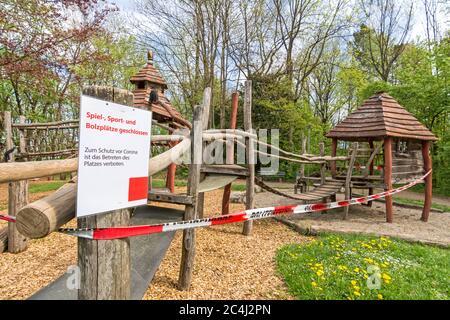 Parque cerrado con cinta de policía y señal de advertencia (texto en alemán: Patio cerrado) debido al virus de la Corona (Covid-19)