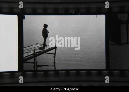 Foto en blanco y negro de un niño parado al final de un muelle mirando las aguas tranquilas. Foto de stock