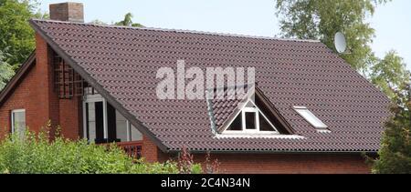 una ventana dorada en un tejado con techo recientemente techado Foto de stock