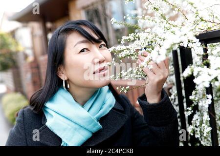 La mujer japonesa posará para una fotografía que sostiene flores en la calle.